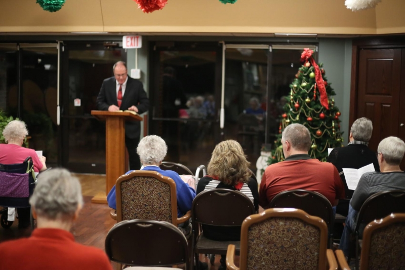 Pastor Bob Koepp, American Lutheran Communities Menomonie residents and families sing a Christmas hy
